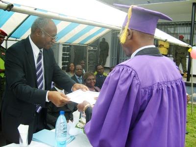 Yang hands certificate to best graduant at Buea Linguistic Centre