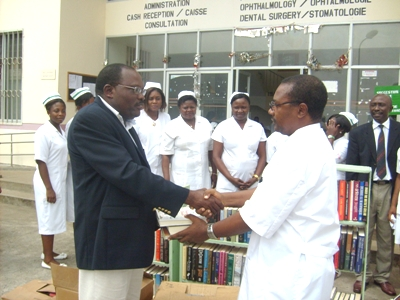 Dr. Fonge (in suit) hands books to Dr. Mbome (in medical gown)