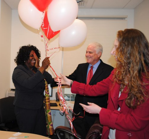 A delighted Joyce Ashuntantang (left) is surprised by President Walter Harrison and student Elizabeth Deer